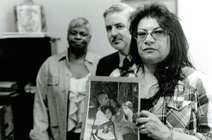 Blanca Bosquez holds a picture of her son while at a meeting with her son's public defender, Ross McMahon, and De-Bug organizer, Gail Noble. Photo by Charisse Domingo.